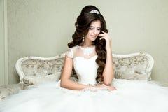Pięknej brunetki elegancka panna młoda z ślubnym makeup i fryzura z diamentowym korony obsiadaniem w rocznika karle Zdjęcie Royalty Free