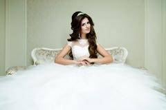 Pięknej brunetki elegancka panna młoda z ślubnym makeup i fryzura z diamentowym korony obsiadaniem w rocznika karle Zdjęcie Stock