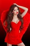 Pięknej brunetki mody dziewczyny wzorcowy pozować w czerwieni sukni z w Obrazy Stock