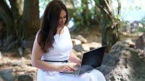 Pięknej brunetki romantyczna kobieta w biel sukni, siedzący na kamieniach i działaniu na laptopie plenerowym, prowadzi jej blog zbiory