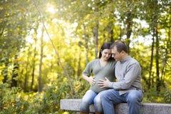 Pięknej ciężarnej pary relaksujący outside w parku Obrazy Stock