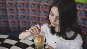 Pięknej dziewczyny porywająca lemoniada z tubule i ono uśmiecha się przy kamerą w kawiarni zdjęcie wideo