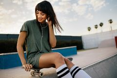 Pięknej dziewczyny słuchająca muzyka z słuchawkami przy łyżwa parkiem obrazy royalty free