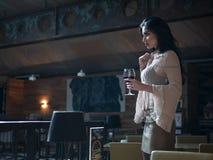 PiÄ™knej dziewczyny wzorcowy pozuje stać z szkÅ'em czerwone wino w jej rÄ™ce w restauracji zdjęcie royalty free