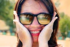 Pięknej i szczęśliwej Azjatyckiej kobiety uśmiechnięty mienie jej twarz jest ubranym okulary przeciwsłonecznych z tropikalnym pla Fotografia Stock