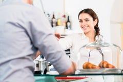 Pięknej kelnerki porci męski klient z filiżanką kawy fo Zdjęcia Royalty Free