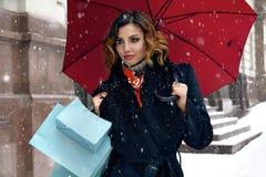 Pięknej kobiety śnieżny uliczny zakup przedstawia Bożenarodzeniowego nowego roku Zdjęcia Stock