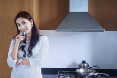 Pięknej kobiety cieszy się wino w kuchni Zdjęcie Royalty Free