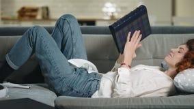 Pięknej kobiety przyglądający photobook na kanapie Zrelaksowana dziewczyna zdejmuje album fotograficznego zbiory