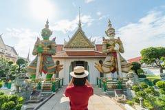 Pięknej kobiety turystyczna Trzymająca kamera chwytać wspominki Wata Arun świątynia w Tajlandia używać jako tło podróży pojęcie z obrazy stock