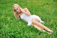 Pięknej młodej żeńskiej blondynki wzorcowy kłaść w polu koniczyna Zdjęcia Stock