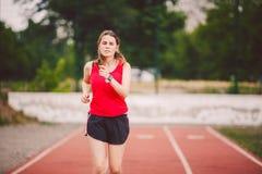 Pięknej młodej atlety Kaukaska kobieta z dużymi piersiami w czerwonej koszulce i skrócie zwiera jogging, biega w stadium z czerwi zdjęcie royalty free