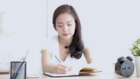Pięknej młodej azjatykciej kobiety uśmiechnięty obsiadanie w nauce pisze w domu żywym izbowym uczenie i notatniku i dzienniczku zbiory wideo