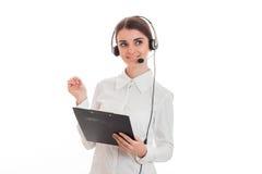 Pięknej młodej brunetki biznesowa kobieta ono uśmiecha się z hełmofonami i mikrofon i robimy notatkom odizolowywać na bielu Zdjęcie Stock