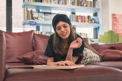 Pięknej młodej brunetki czytelnicza książka w bookstore Zdjęcie Stock