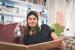 Pięknej młodej brunetki czytelnicza książka w bookstore Zdjęcie Royalty Free