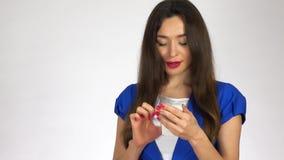 Pięknej młodej brunetki kobiety pisać na maszynie wiadomości tekstowe na jej telefonie komórkowym zdjęcie wideo