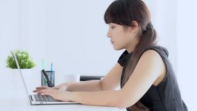 Pięknej młodej freelance azjatykciej kobiety uśmiechnięty działanie i pisać na maszynie na laptopie przy biurka biurem z profesjo zbiory wideo