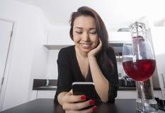 Pięknej młodej kobiety czytelnicza wiadomość tekstowa na mądrze telefonie przy kuchennym kontuarem zdjęcia stock