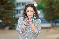 Pięknej młodej kobiety podmuchowi confetti i mieć zabawa outdoors obrazy royalty free