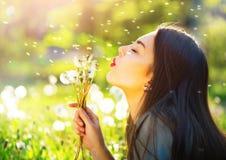 Pięknej młodej kobiety podmuchowi dandelions Zdjęcia Stock