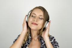 Pięknej młodej kobiety słuchająca muzyka w hełmofonach odizolowywał białego tło obraz royalty free