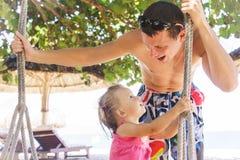 Pięknej małej dziewczynki siedząca arkana huśta się na plaży Tata spojrzenia przy jego córką i one są uśmiechnięci fotografia royalty free