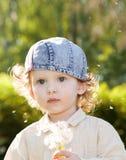Pięknej małej kędzierzawej dziewczyny podmuchowy dandelion Zdjęcia Stock
