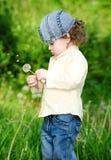 Pięknej małej kędzierzawej dziewczyny podmuchowy dandelion, vertical strzał Obrazy Stock