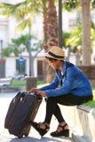 Pięknej murzynki siedzący outside z walizką Zdjęcia Royalty Free
