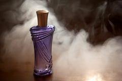 Pięknej purpury butelki żeński pachnidło w dymu Zdjęcie Royalty Free
