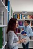 Pięknej rudzielec dziewczyny mienia studencka książka w bibliotece z Zdjęcie Stock
