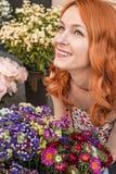 Pięknej rudzielec Kaukaska dziewczyna wącha kolorowych kwiaty w ogródzie Obraz Stock