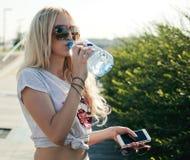 Pięknej sprawności fizycznej atlety młodej kobiety blond woda pitna po opracowywał ćwiczyć na zmierzchu wieczór lecie w plażowym  Obrazy Stock