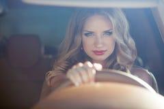 Pięknej Uśmiechniętej kobiety napędowy samochód, atrakcyjny dziewczyny obsiadanie wewnątrz zdjęcia stock