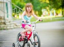 Pięknej uśmiechniętej małej dziewczynki jeździecki bicykl Zdjęcia Stock