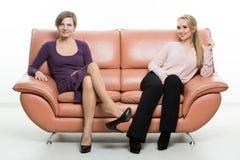 Piękni żeńscy przyjaciele na kanapie Dwa zdjęcia royalty free
