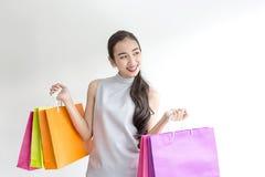 Piękni azjatykci dziewczyny przewożenia torba na zakupy tło odizolowane na zakupy uśmiechniętym białą kobietę piękna dziewczyna a Fotografia Royalty Free