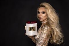 Piękni blondyny modelują w eleganckiej sukni trzyma prezent, kwiatu pudełko z różami prezenta valentine s zdjęcie royalty free