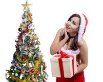Piękni boże narodzenia uśmiecha się Egipskiej dziewczyny w Santa Claus kostiumu z prezenta pudełkiem obok choinki Obrazy Stock