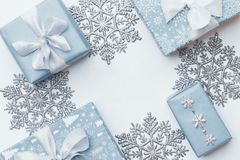Piękni boże narodzenie prezenty i srebni płatki śniegu odizolowywający na białym tle Pastelowi błękitni barwioni zawijający xmas  obraz royalty free