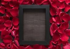 Piękni czerwieni róży płatki i rama obrazek są na drewnianych półdupkach Zdjęcie Stock
