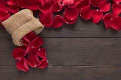 Piękni czerwieni róży płatki są na drewnianym tle Zdjęcia Stock