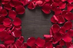 Piękni czerwieni róży płatki są na drewnianym tle Obrazy Stock