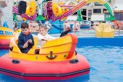 Piękni dzieci ma zabawę przy parkiem rozrywki Dzieci dalej zdjęcia stock
