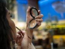 Piękni dziewczyn spojrzenia w małym lustrze i farbach jej wargi z warga liniowem obraz royalty free
