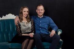 Piękni enamored potomstwa dobierają się w klasyków ubraniach siedzą na błękitnym Zdjęcie Royalty Free