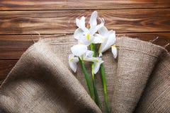 Piękni irysy zawijający w burlap tkaninie na drewnianym stole, odgórny v obraz stock