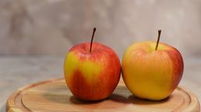 Piękni jabłka na drewnianej desce Zdjęcia Royalty Free
