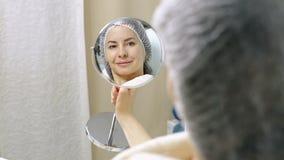 Piękni kobiet spojrzenia przy ona w lustrze po kosmetycznych procedur w piękno salonie zbiory wideo